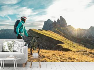 Young man with mountain bike on Seceda mountain peak at sunrise. Puez Odle, Trentino, Dolomites, Italy.