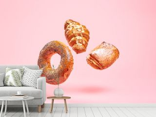 Croissant bun brioche cake flying in air. Fresh baked puff pastry cookie falling on white. Delicious french baking croissant with almond. Levitation, fly bread bakery products cafe concept on pink