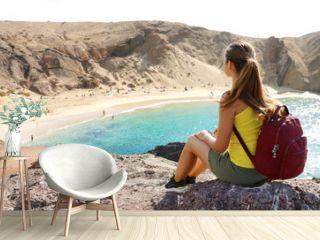 Beautiful young backpacker admiring Playa Papagayo beach in Lanzarote, Canary Islands, Spain