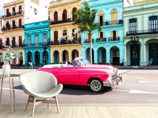 old pink convertible classic car in front of colorful houses in havana cuba