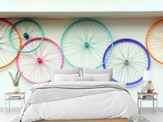 Old bicycle wheels colorful on the wall of a rental and repair shop, hipster decorative trend concept