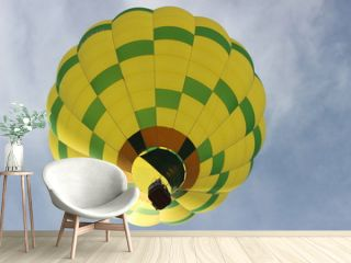 Yellow and Green Hot Air Balloon In Flight Close Up From Below