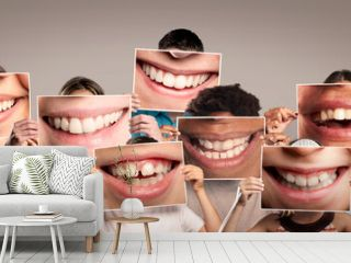 group of happy people holding a picture of a mouth smiling on a gray background