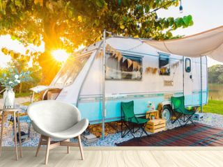 Camping chairs placed outside cozy retro travel trailer Caravan under tree before sunset near the river in peaceful countryside. Outdoor and Recreational Vehicles Theme. Travel Industry.