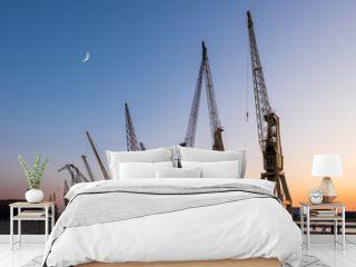 Old harbor crane silhouettes under a crescent moon. Antwerp, Belgium.