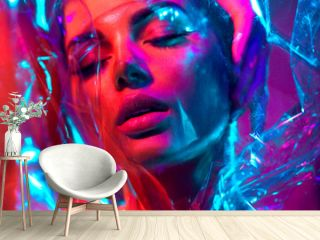 High Fashion model girl in colorful bright neon lights posing in studio through transparent film. Portrait of beautiful young woman in UV. Art design colorful make up. On colourful vivid background