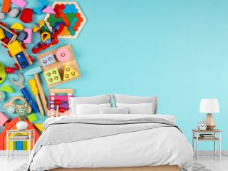 Baby kids toys on light blue background. Colorful educational wooden, plastic, fluffy and musical toys. Top view, flat lay