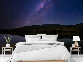 Starry night sky. The milky way is reflected in the lake. The mountains are sleeping peacefully.