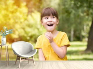 Surprised little girl in a yellow t-shirt on a green background