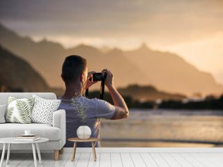 Rear view of man during photographing landscape with cliff. Photographer on beach at moody sunset. Tenerife, Canary Islands, Spain.