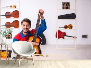 Young male repairman repairing musical instruments at workplace