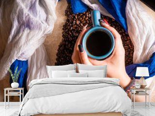 manos femeninas con una taza de café sobre granos de café con fondo de mármol y telas azules y blancas