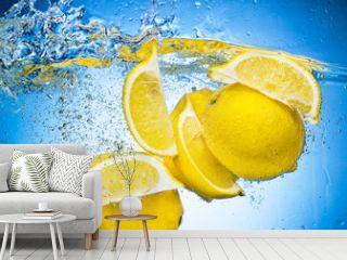 Lemon Slices falling deeply under water with a big splash on blu