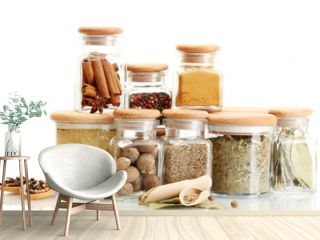 jars and wooden spoons with spices isolated on white