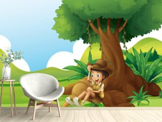 A young boy and a cat under the big tree