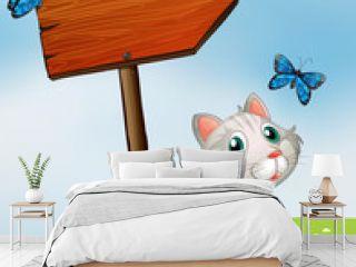A cat with three butterflies beside the wooden arrow board