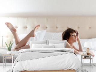 Smiling brunette posing on hotel bed