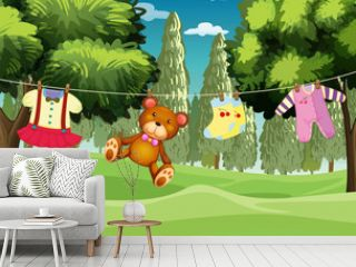 A teddy bear and clothes hanging