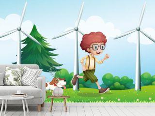 A boy running with a dog near the three windmills