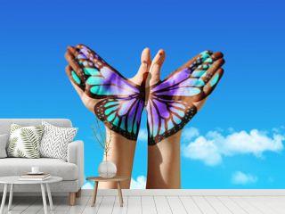 Hand and butterfly hand painting, tattoo, over a blue sky