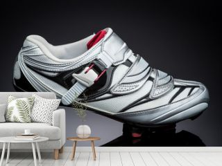 one road cycling shoe standind at small metal sprocket