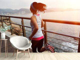 fitness woman running at seaside wooden bridge
