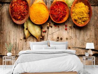 Spices. Curry, saffron, turmeric, cinnamon over wood