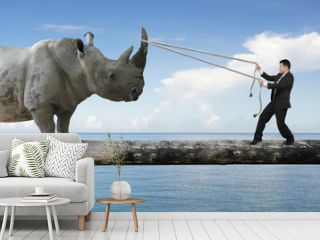 Businessman pulling rope against rhinoceros balancing on tree tr
