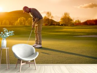Male golf player putting at sunset.