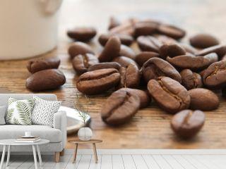grains de café en gros plan et tasse de café et cuillère sur table en vieux bois