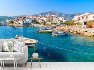 Fishing boats in Kokkari bay with colourful houses in background, Samos island, Greece