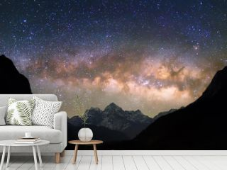 """Bowl of Heavens. Bright and vivid Milky Way galaxy over the snowy mountains. Beautiful starry night sky seems to be in a """"bowl"""" between the silhouetted hills."""
