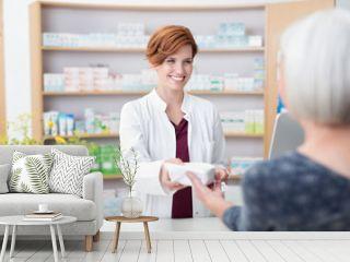 ältere dame kauft medimamente in der apotheke