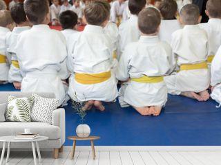 Children in kimono sitting on tatami on martial arts seminar. Selective focus