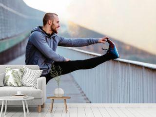 Athletic runner doing stretching exercise, preparing for morning