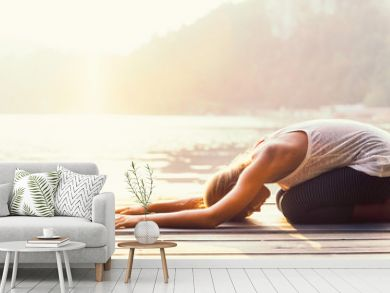 Sun salutation yoga. Young woman doing yoga by the lake, bathing in sunlight.
