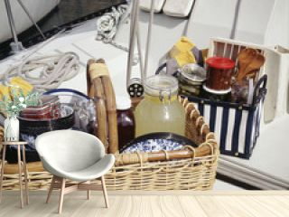 Food items with tableware in picnic basket on sailboat