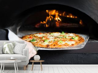 Hot pizza is removing from hot slove where it was baked. Cook using special shovel to removing them. This restaurant have special wood-fired oven.