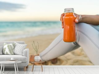 Healthy carrot vegetable juice detox cleanse woman drinking smoothie for weight loss diet at beach sunset. Closeup of fresh orange glass bottle. Juicing trend, raw, organic and cold-pressed.