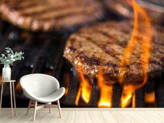 Mehrere Burger auf dem Grillrost mit Flammen im Vordergrund