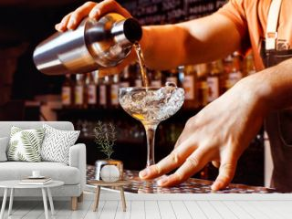 Male bartender is making cocktail holding shaker with pouring alcohol
