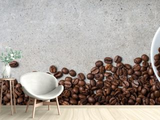 Cup of coffee with coffee beans on gray stone background. Top view