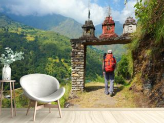 Tourist, a man, enter the gate to nepalese village at the valley on Annapurna Circuit Trek, in Annapurna Himal, Himalaya, Nepal, Asia