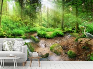 Enchanting panoramic forest scenery with soft light falling through the foliage, a stream with tranquil water and a heron