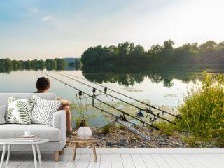 Fishing adventures, carp fishing. Angler is fishing with carpfishing technique in a beautiful summer day