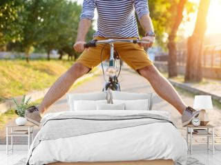 Close up of hipster man riding bicycle with his legs in the air
