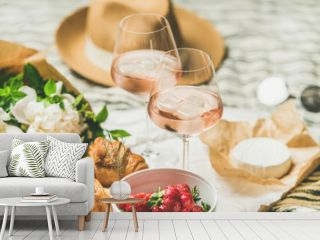 French style romantic summer picnic setting. Flat-lay of glasses of rose wine with ice, fresh strawberries, croissants, brie cheese, straw hat, sunglasses, peony flowers. Outdoor gathering concept