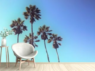 Retro styled upward view of a group of tall palm trees against blue sky