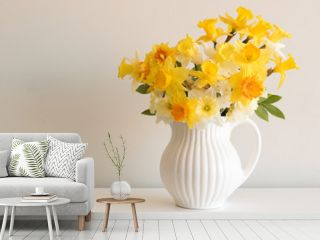 Close up of varied yellow daffodils in white jug on table against neutral wall background