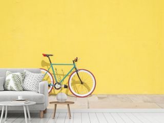 A City bicycle fixed gear on yellow wall